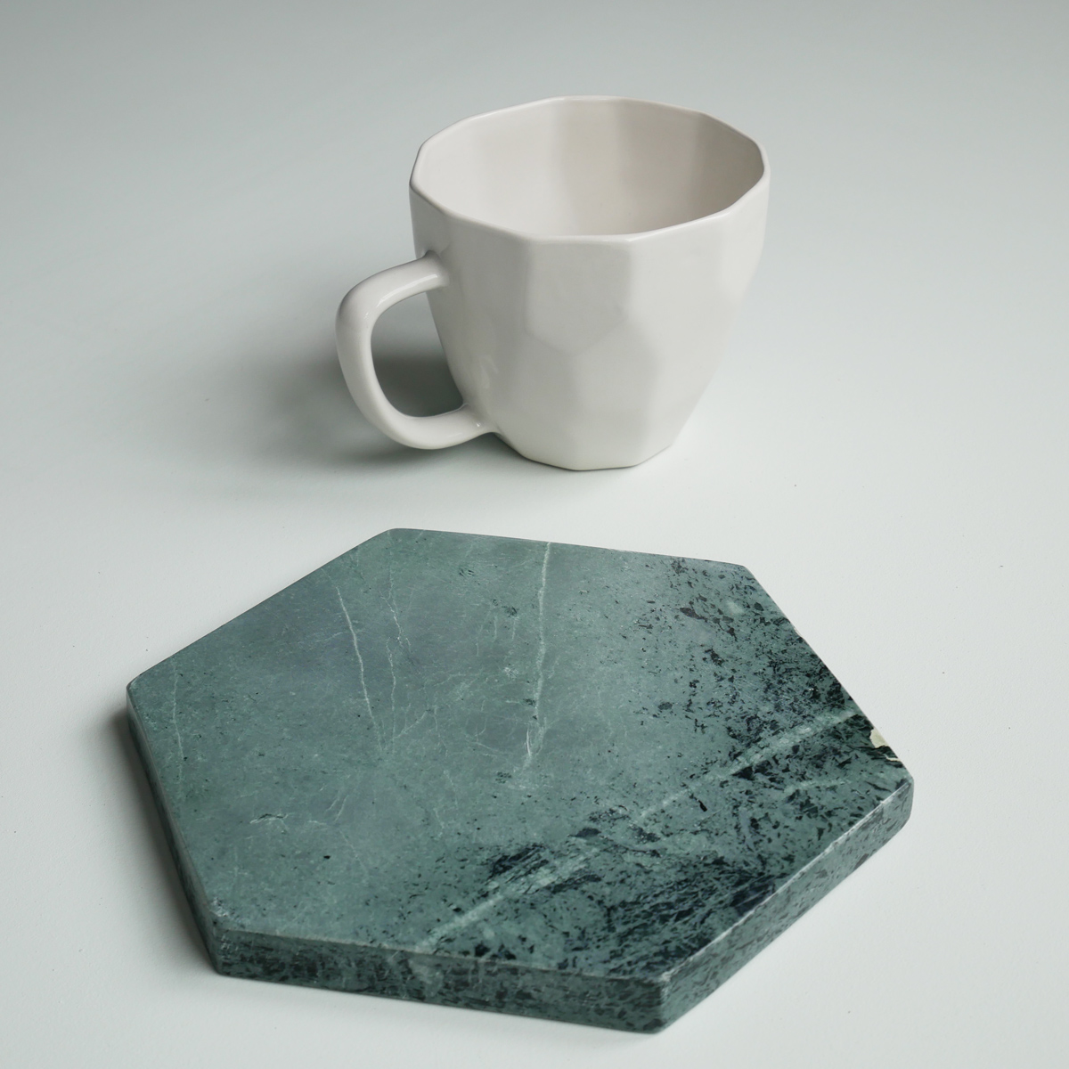 white-geometric-mug-next-to-green-hex-marble-liv-interior